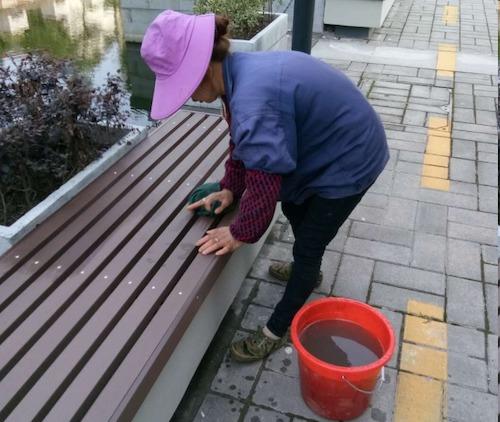 9、烈日下,物业员工余红花非常认真地在擦露天凳子.