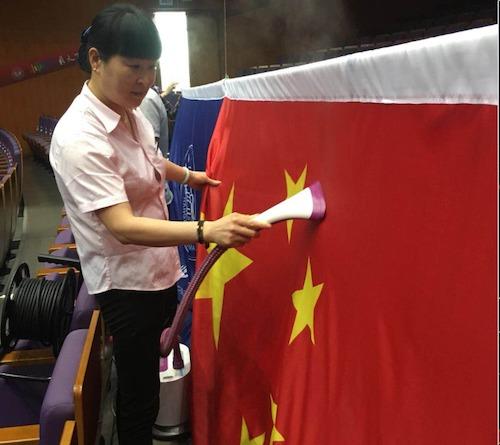 12、会务部员工细心地熨烫校庆纪念大会上用的国旗