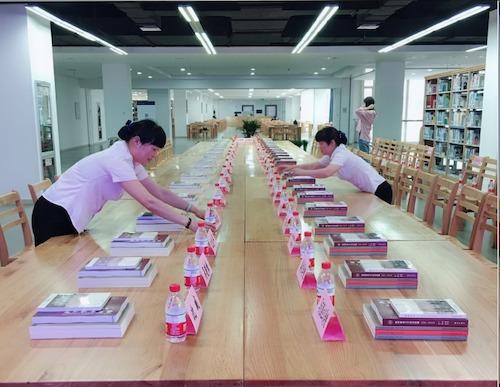 15、会务员工整齐地码好会议材料,为学校110周年校庆系列书籍发布会做准备.