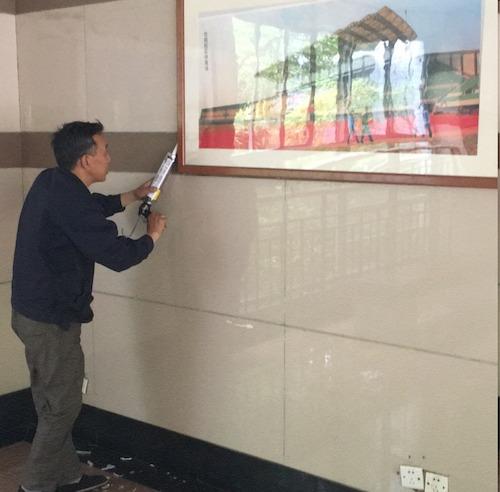 17、下沙物业维修部员工专注于打玻璃胶挂画..
