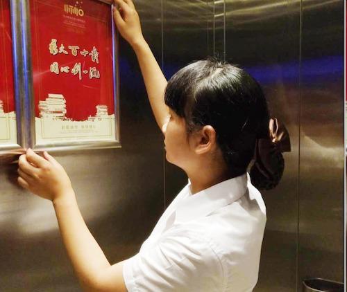 20、交流中心员工正在布置电梯内宣传牌.