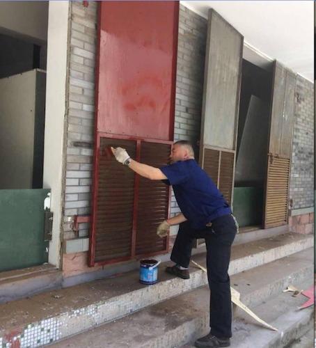 玉皇山物业员工给高配房门刷上新的油漆,展现校园新面貌